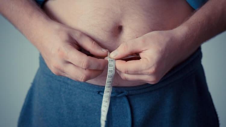 男性がお腹周りを測る